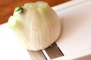 Der Fenchel wird mit einem Gemüsehobel in hauchdünne Scheiben geschnitten.