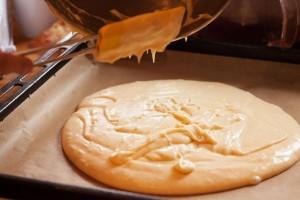 Der Rührteig für den Butterkuchen wird auf Backpapier vorgebacken.