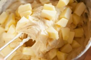 Die Apfelstücke werden mit einem Teigschaber unter den Rührteig gehoben.