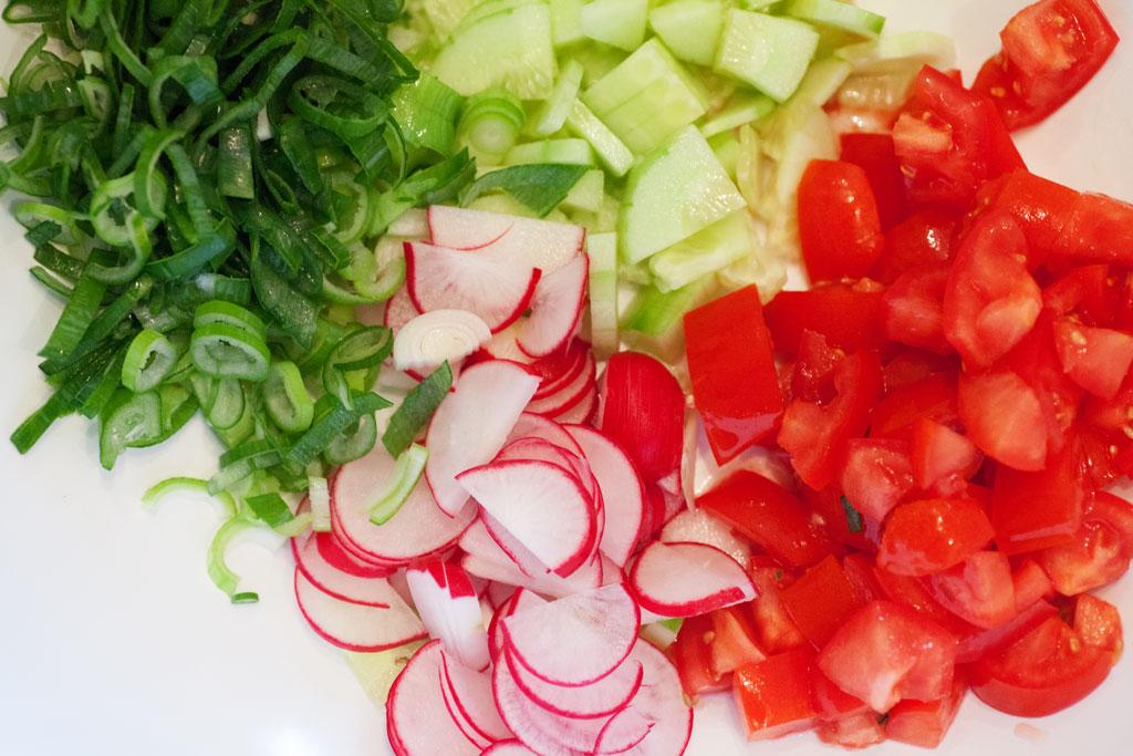 Die Gemüsesorten werden für den gemischten Salat in feine Stücke geschnitten.
