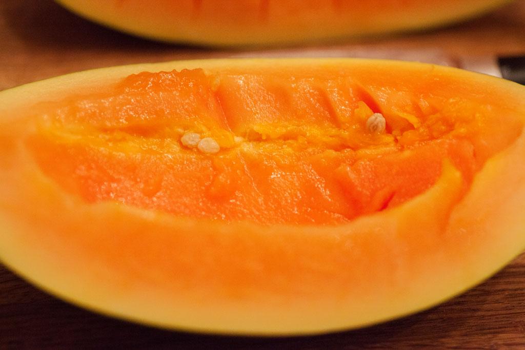 Die Papaya wird längs halbiert und die Kerne mit einem Löffel herausgelöst.