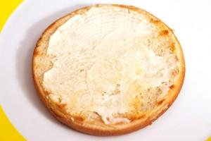 Die Schnittfläche des Hamburgerbrötchens wird mit Mayonnaise bestrichen.