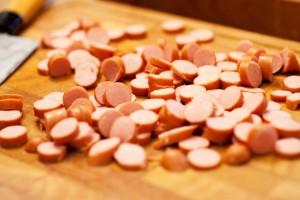 Die Wiener Würstchen werden in Scheiben geschnitten.