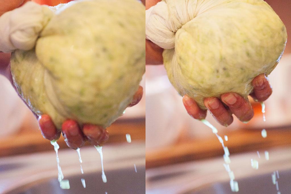 Die Zucchiniraffel werden in einem Seihtuch ausgedrückt damit sie Wasser verlieren.