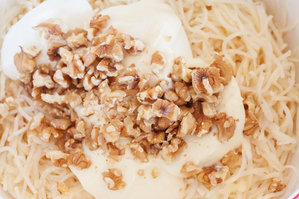 Die Zutaten für den Waldorfsalat werden vermengt und mit Salz, Pfeffer und Zitronensaft abgeschmeckt.