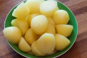Die fertig gegarten Kartoffeln auf einem Teller zwischenlagern...
