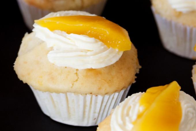 Die fertigen Muffins werden mit Mangosahne und Mangostreifen belegt.