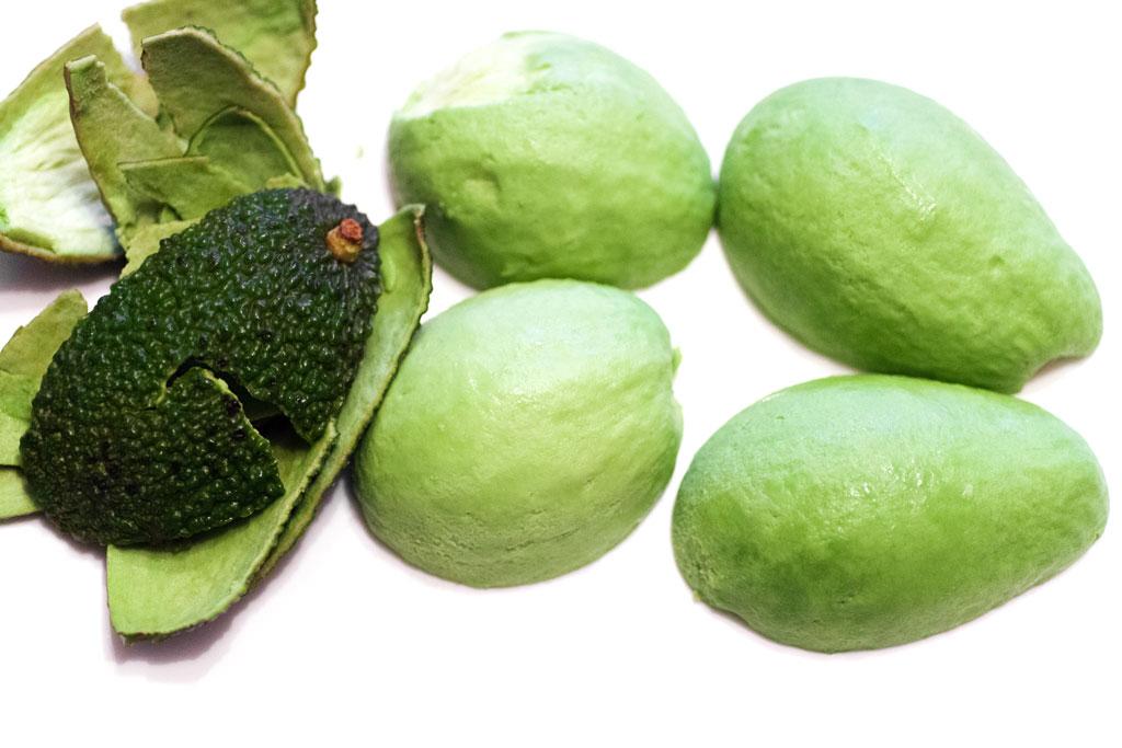 Die geschälten Avocadohälften werden mit der flachen Seite nach unten auf einen Teller gelegt.