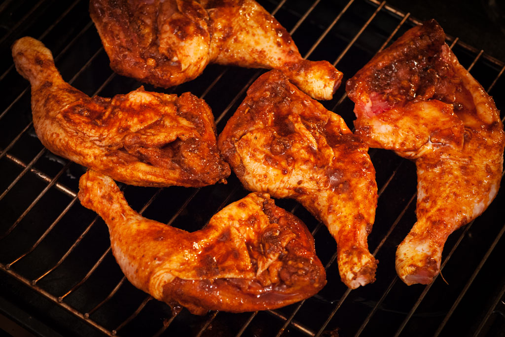 Die knusprigen Hähnchenschenkel im Ofen werden auf einem Rost gebacken.