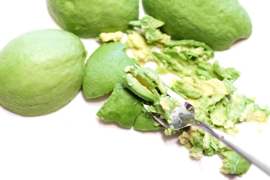 Die reife Avocado wird für die Guacamole mit Zwiebeln mit einer Gabel zerdrückt.