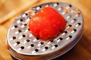 Die reife Tomate wird bis auf die Schale gerieben.