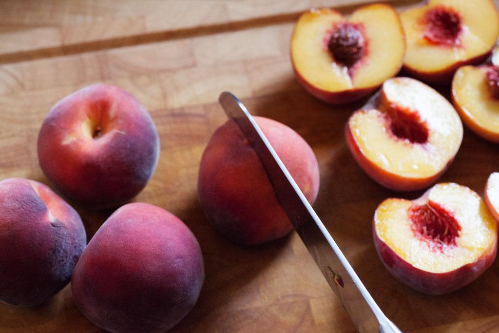 Die reifen Pfirsiche mit einem scharfen Messer halbieren und entkernen.