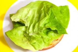 Die untere Hälfte des Hamburgerbrötchens wird mit Salat bedeckt.
