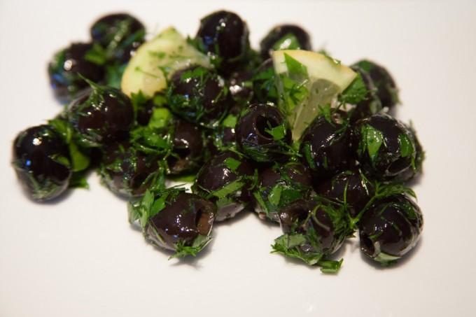 Eine Portion eingelegte-Oliven-mit-frischem-Dill-und-Petersilie.