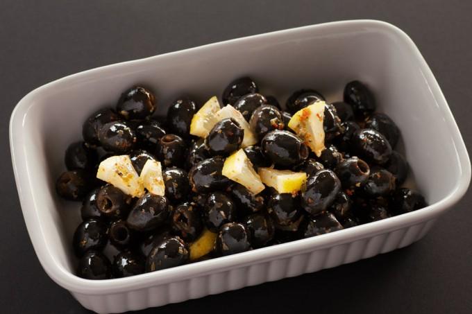 Eingelegte schwarze Oliven mit Zitrone, Chili und Oregano.