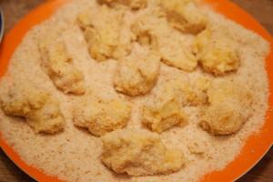 Fertig panierte Hühnchenkroketten werden auf einem Teller bereitgelegt.