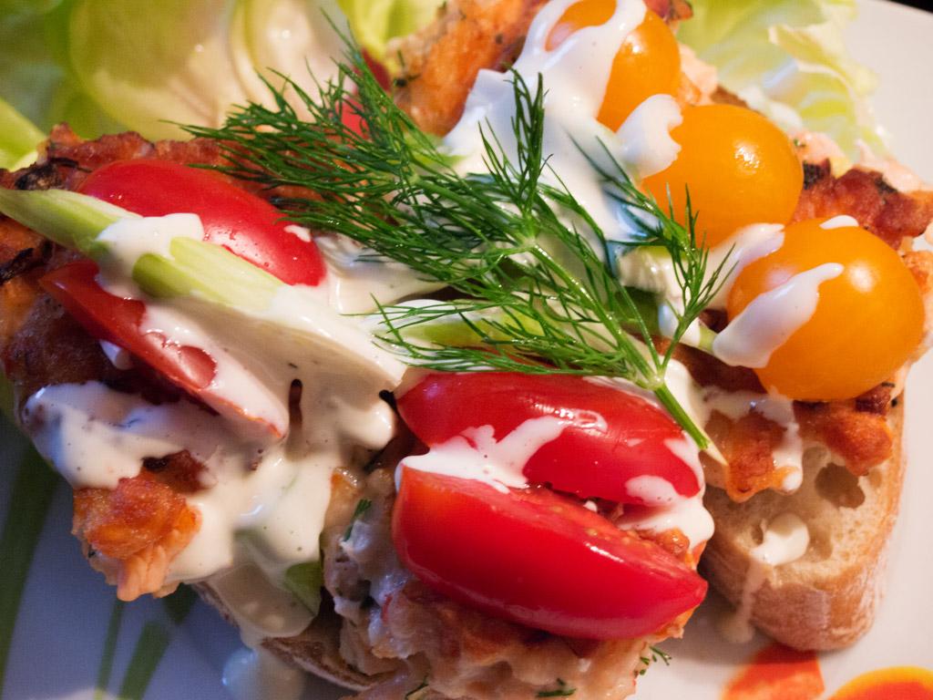 Fischburger mit frischen Tomaten, Frühlingszwiebel und Dill.