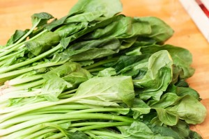 Frischer Spinat wird gewaschen und die Blätter von den Stielen getrennt.
