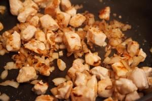 Hühnchen wird mit Zwiebeln in Öl angebraten.