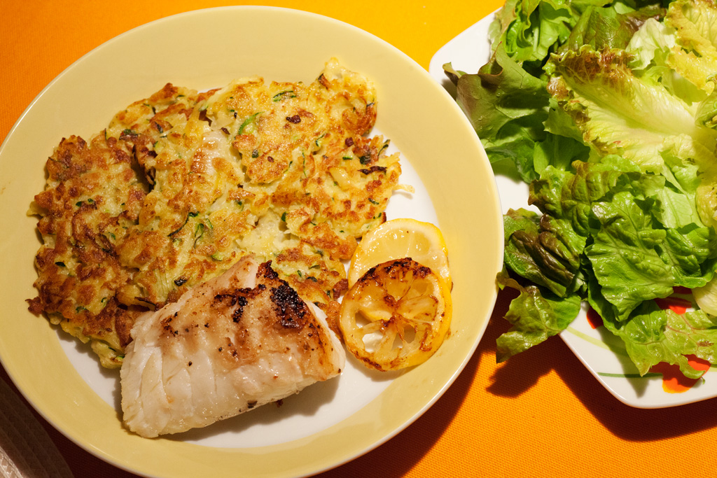 Kabeljaufilet mit Zucchini-Kartoffelrösti und Salat mit Joghurtsauce.