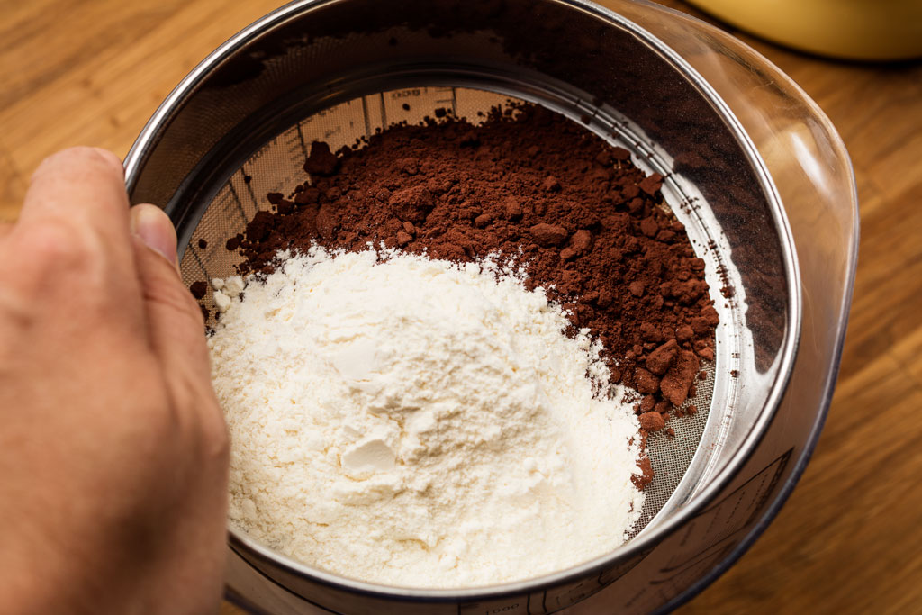 Flour and unsweetened cocoa powder are sifted through.