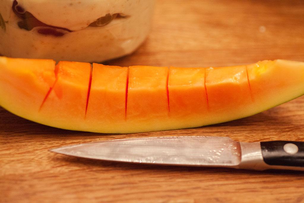 Papaya wird in Stücke geschnitten. Die Schale wird entfernt.