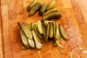 Saure Gurken werden für die Hamburger und Cheeseburger in dünne Scheiben geschnitten.