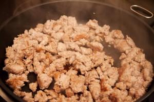 Thüringer Mett wird in Öl angebraten und beim braten zerkleinert.
