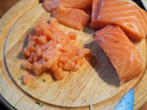 Tiefgekühlter Lachs wird aufgetaut und in kleine Würfel geschnitten.