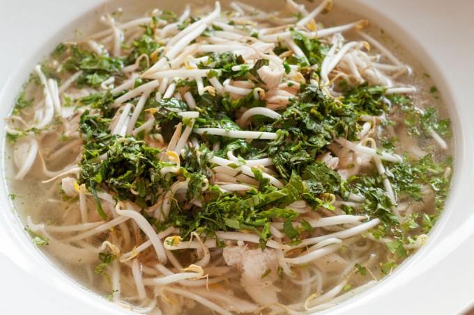 Vietnamesische Hühnersuppe pho ga mit frischen Kräutern und Reisnudeln.