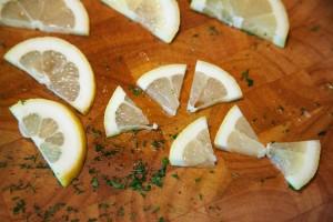 Zitrone wird für die eingelegten Oliven in Stücke geschnitten.