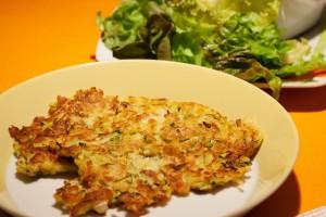 Zucchini-Kartoffelrösti mit Salat.
