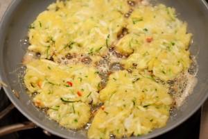 Zucchini-Kartoffelrösti werden in Öl gebraten.