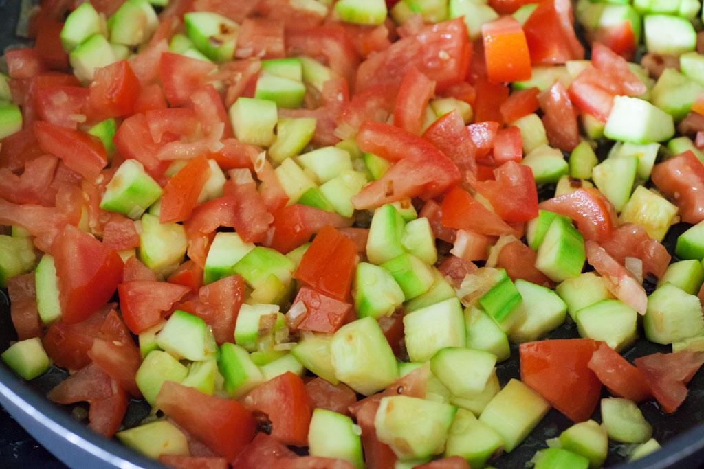 Zucchini- und Tomatenstücke werden angebraten.