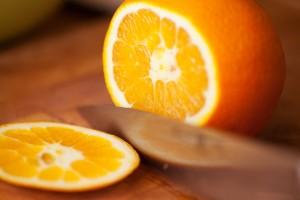 Zum Filetieren der Orange werden zuerst der Boden und die Oberseite abgeschnitten.