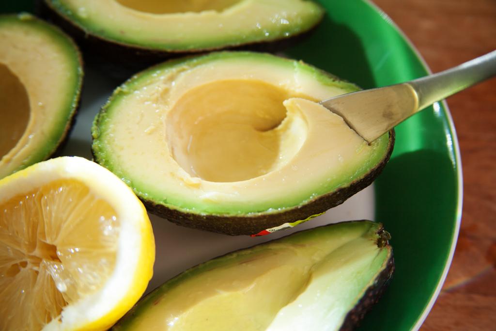 Halbierte und entkernte Avocados werden gesalzen und mit Zitronensaft übergossen,